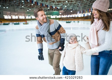 Happy family at skating rink - stock photo