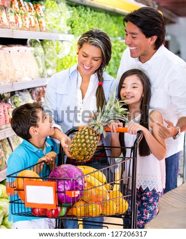 Happy family at the supermarket shopping for groceries - stock photo
