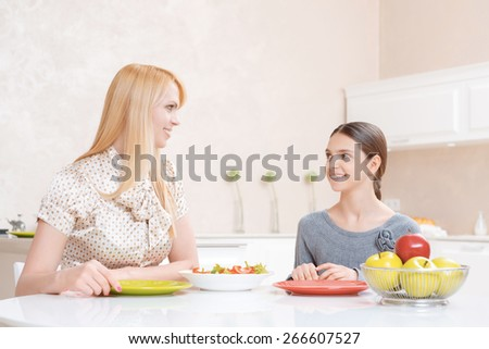 Happy family. Attractive blond mother and pretty teenage girl smiling at each other having lunch together at home kitchen - stock photo
