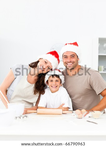 Happy family baking christmas cookies together in the kitchen - stock photo