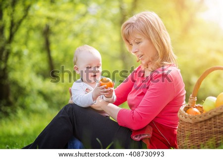 Happy family.Beautiful middle aged mother and her adorable little son having a picnic in sunny park. - stock photo