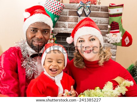 Happy family: black father, mom and baby boy dressed costume Santa Claus by fireplace. Christmas and New Year. - stock photo