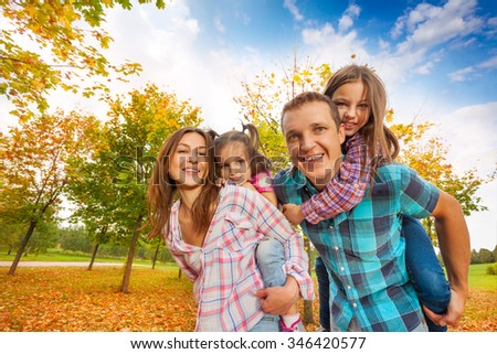 Happy family carry little girls in the autumn park - stock photo