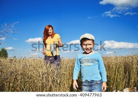 Happy family. Caucasian pregnant woman and her son having fun in park - stock photo
