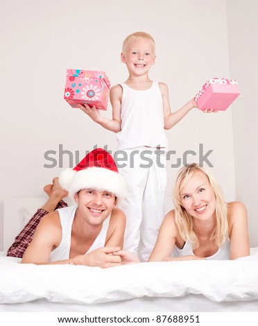 happy family celebrating Christmas and opening presents: mother ,father and their son on the bed at home - stock photo