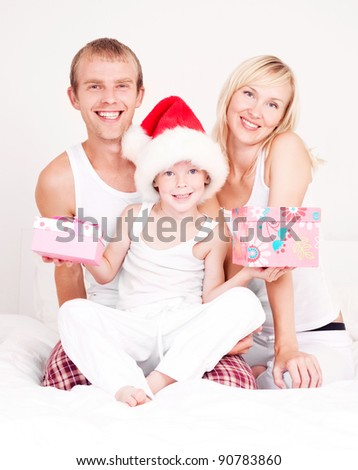 happy family celebrating Christmas and opening presents, sitting on the bed at home - stock photo