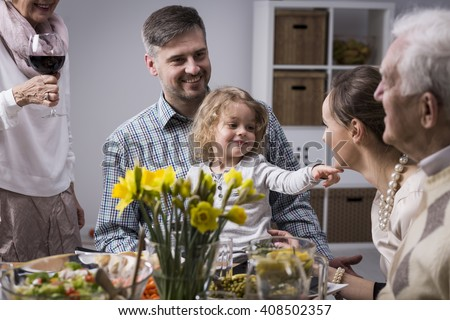 Happy family celebrating mother's day, sitting beside table during dinner - stock photo