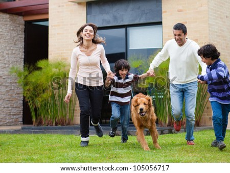 Happy family chasing a dog and having fun - stock photo