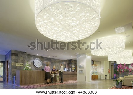 Happy family checking in at the reception desk - stock photo