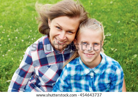 Happy family. child and happy parent concept - hugging mother and daughter - stock photo