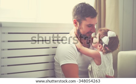 happy family child baby girl in the arms of his father at home window - stock photo