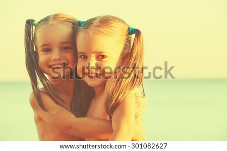 happy family children twin sisters on the beach at Sea - stock photo