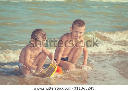 Happy family. Children - two boys having fun on the beach. Positive human emotions, feelings, emotions. - stock photo
