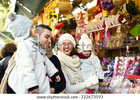 Happy family choosing Christmas decoration at Christmas market. Focus on woman and her daughter - stock photo