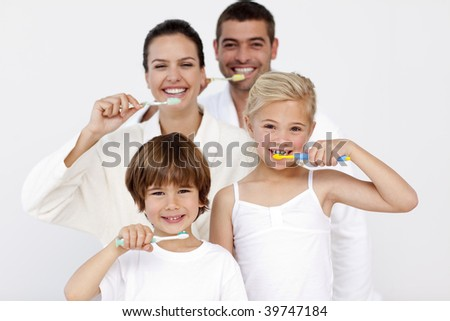 Happy family cleaning their teeth in bathroom - stock photo