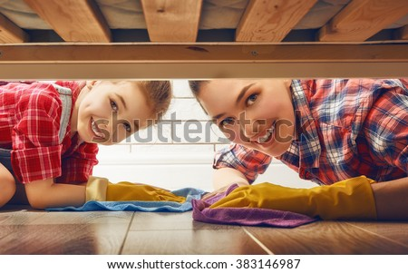 Happy family cleans the room. Mother and daughter do the cleaning in the house. A young woman and a little child girl wiped the floor. - stock photo