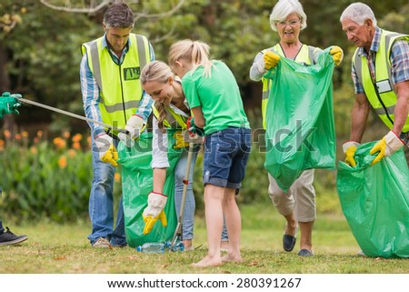 Happy family collecting rubbish on a sunny day - stock photo