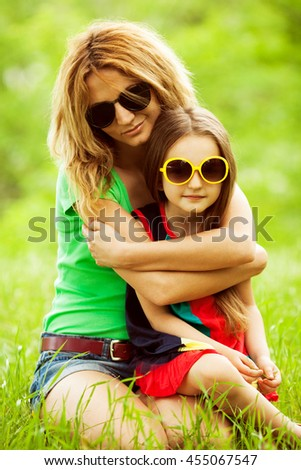 Happy family concept. Baby girl with long brown hair and her mother with blond hair in trendy eyewear sitting together in park. Outdoor shot - stock photo