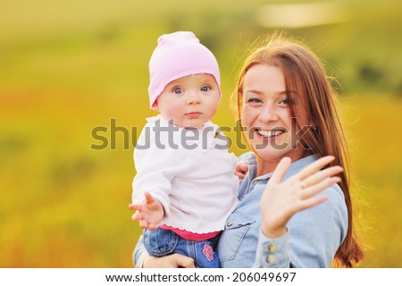 Happy family concept, mom and lovely daughter at sunny field. - stock photo