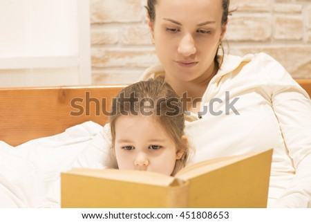 Happy family concept. Mother and her little lovely daughter, concept of togetherness. Mother reading bedtime stories to her beautiful little girl while sitting on the bed at home - stock photo