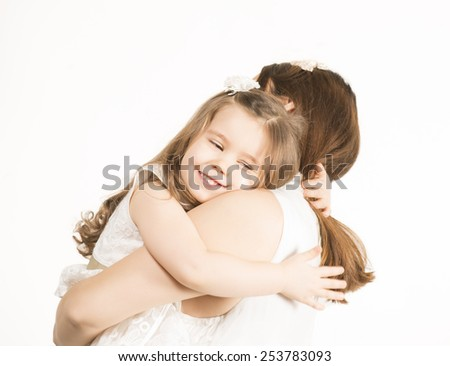Happy family concept. Mother and her little lovely daughter, concept of togetherness, studio shot. Beautiful little girl embracing her mother on white background - stock photo