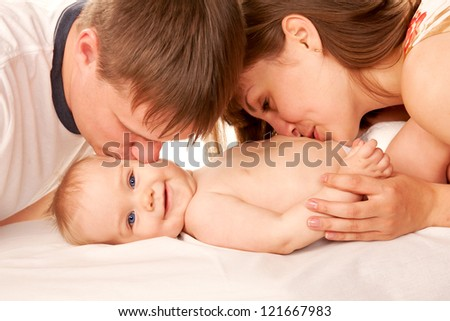 Happy family concept. Parents kissing the kid, the baby smiling. Isolated on white background. - stock photo