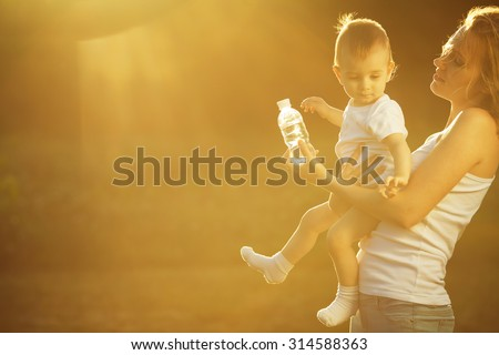 Happy family concept. Playing mother and little son in white casual sleeveless shirts. Toddler in white socks, diaper holding bottle of water. Rays of light at summer sunrise. Copy-space. Outdoor shot - stock photo