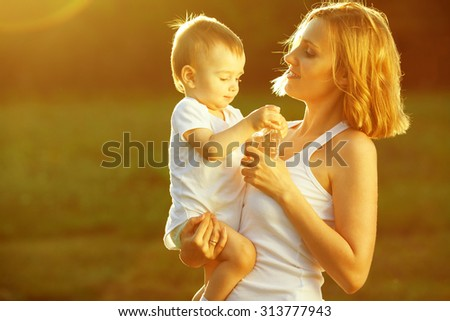 Happy family concept. Portrait of playing mother and little son in white casual sleeveless shirts. Toddler in white socks, diaper holding bottle of water. Rays of light at summer sunrise. Outdoor shot - stock photo