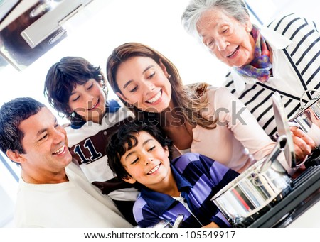 Happy family cooking together at home and smiling - stock photo