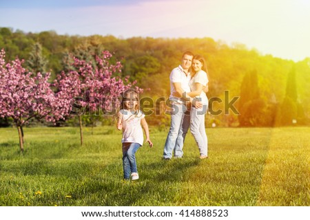 Happy family: cute little girl running in sunset light, her parents hugging on the background - stock photo