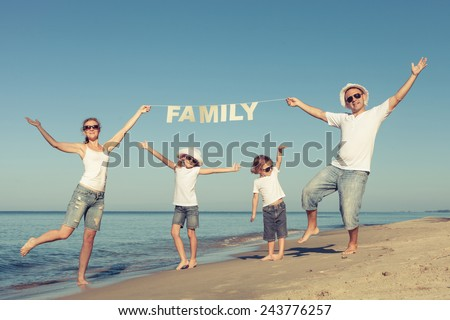 Happy family dancing on the beach at the day time. Concept of friendly family. - stock photo