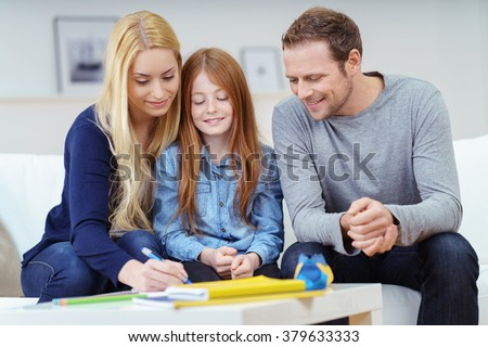 Happy family doing homework together as the parents help their attractive young redhead daughter with her class work on the sofa at home - stock photo