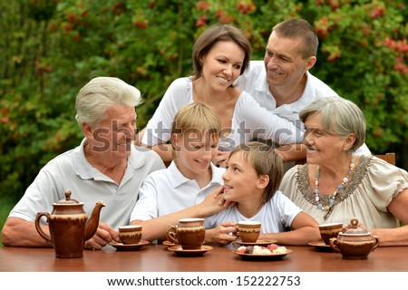 Happy family drinking tea at table outdoors in summer time - stock photo