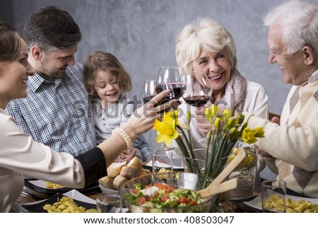 Happy family during holiday dinner, smiling, talking, drinking red wine - stock photo