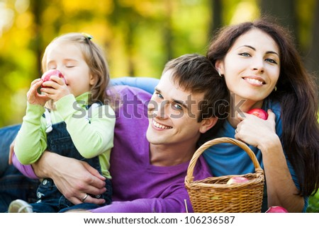 Happy family eating apples in autumn park - stock photo