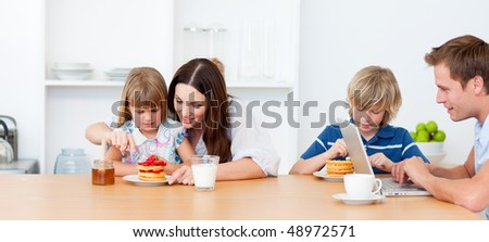 Happy family eating breakfast in the kitchen at home - stock photo