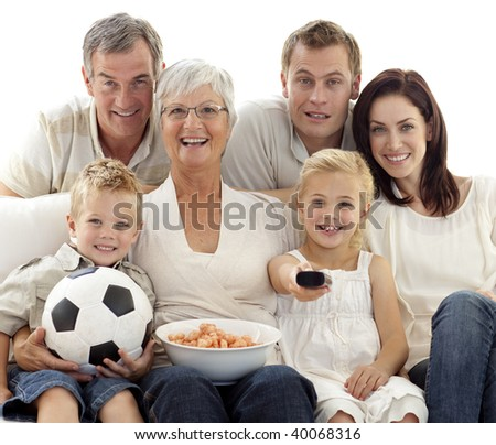 Happy family eating crisps and watching a football match at home - stock photo