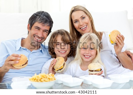 Happy family eating hamburgers sitting on the floor at home - stock photo