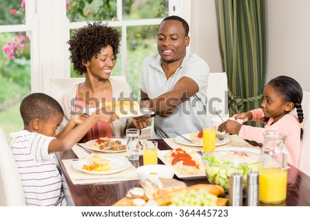 Happy family eating together at home - stock photo