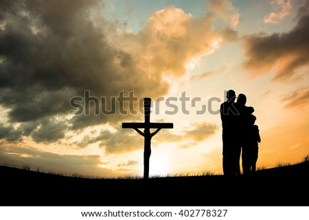Happy family embracing each other over against cross religion symbol shape over sunset sky - stock photo