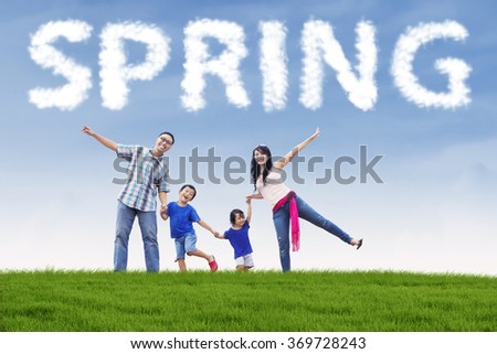 Happy family enjoy freedom while holding hands on the field under a spring cloud - stock photo