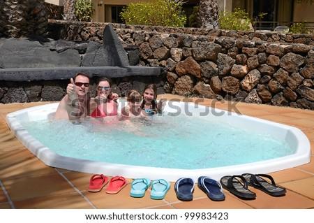 Happy family enjoy the tropical jacuzzi - stock photo