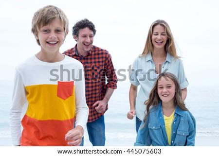 Happy family enjoying at beach against sky - stock photo