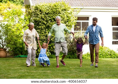 Happy family enjoying on grass outside house at yard - stock photo