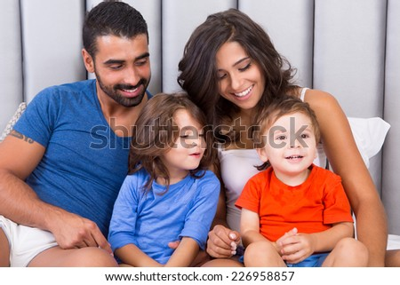Happy family enjoying the morning in bed - stock photo