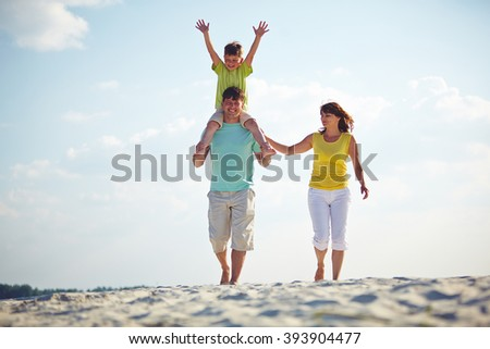 Happy family enjoying the time on the beach together - stock photo