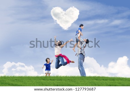 Happy family enjoying Valentine's day in the park - stock photo