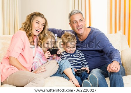 Happy family enjoying video games together at home - stock photo