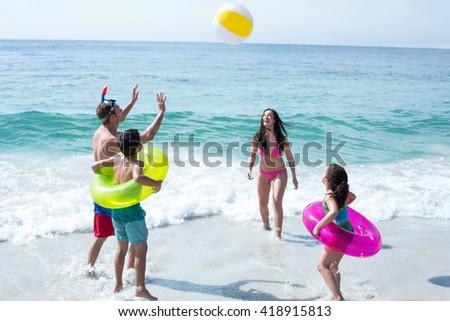 Happy family enjoying with beach ball on sea shore at beach - stock photo
