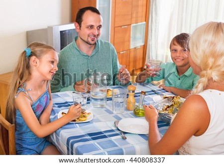Happy family family  with two kids dining together and talking at home - stock photo